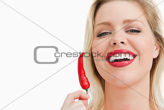 Blonde woman holding a chili while laughing