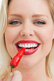 Happy blonde woman eating a chili
