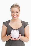 Woman showing a pink piggy bank