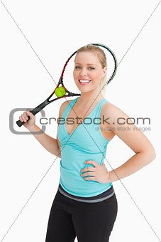Woman smiling while holding a racquet behind her head