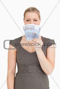 Pretty woman hiding her mouse with euro banknotes