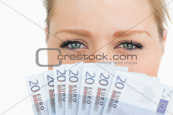 Close up of a woman face hidden with euro banknotes