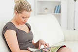 Woman sitting while reading a magazine