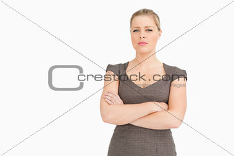 Uneasy woman standing with her arms crossed