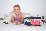 Blonde lying on her bed next to a full suitcase