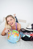 Student with a suitcase pointing on an earth globe