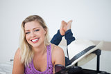 Young blonde smiling behind a suitcase