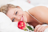 Blue eyed woman smiling with a rose
