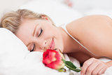 Smiling woman with a rose sleeping