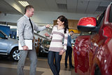 Salesman giving car keys to a woman