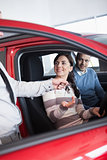 Smiling woman receiving keys from a salesman while sitting
