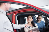Couple sitting in a car receiving key from a car dealer