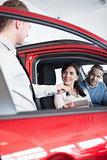Smiling customer receiving car keys