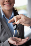 Hand holding keys over the hand of a woman