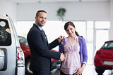 Salesman shaking hand and giving keys to a woman