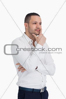 Thoughtful man standing and crossing his arms
