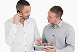 Two people discussing while phoning and holding a tablet compute