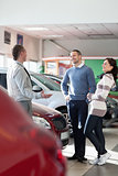 Smiling couple talking with a car dealer