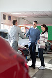 Car dealer shaking hand with a man