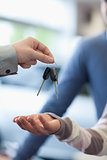Salesman holding keys over the hand of a customer
