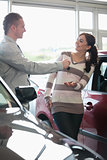 Smiling woman receiving keys from a salesman