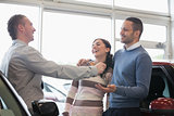 Laughing couple receiving keys from a salesman