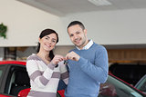 Smiling couple standing next to a car