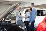 Man shaking hand of a car dealer in front of a car