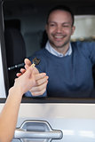 Man in a car receiving a key