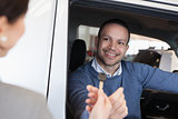 Man smiles as he takes a car key
