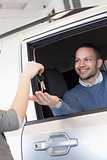 Smiling man in a car receiving a car key