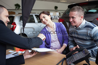 Couple chatting with a car salesman