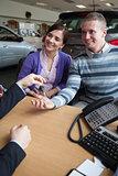 Happy couple receiving keys from a salesman