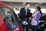 Salesman talking to a smiling woman next to a car