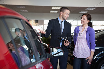 Salesman showing a car to a woman