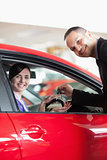 Happy salesman giving car keys to a woman