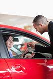 Smiling woman receiving car keys