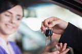 Woman in a car receiving keys