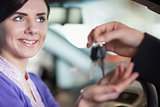 Woman smiles as she takes car keys