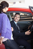 Man sitting in a car while talking to a woman