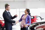 Salesman shaking the hand of a woman and giving her car keys