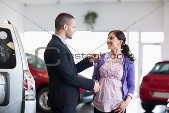 Woman shaking the hand of a salesman while receiving car keys