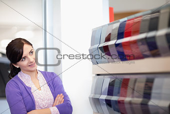Woman crossing arms while looking at a color palette