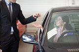 Smiling woman in a car taking keys