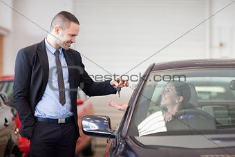 Salesman smiling while giving keys to a woman