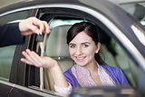 Smiling woman smiles as she sits in a car