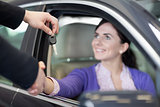 Woman in a car while shaking a hand and receiving car keys