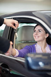 Woman smiling in a car while shaking hand