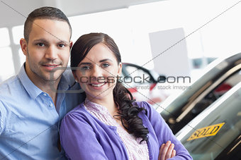 Couple hugging in front of a car