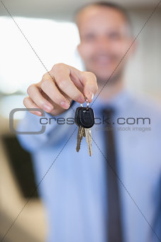 Salesman holding car keys by his fingertips